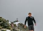 Patrick mit dem Gipfelkreuz im Hintergrund